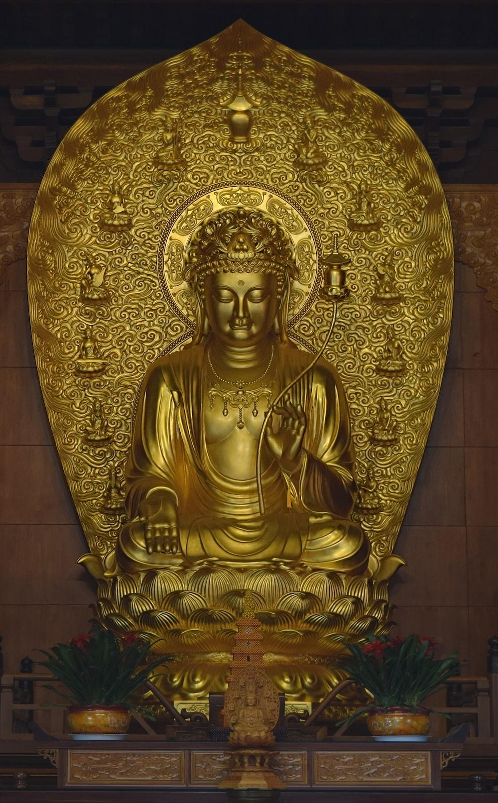 gold buddha statue on brown floor tiles