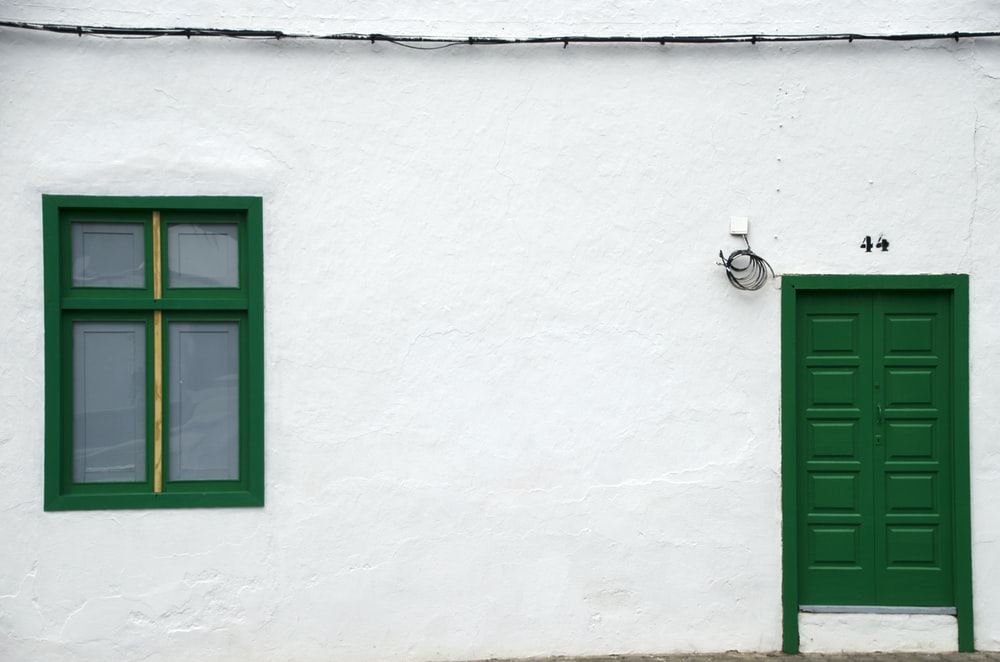 green wooden window frame on white concrete wall