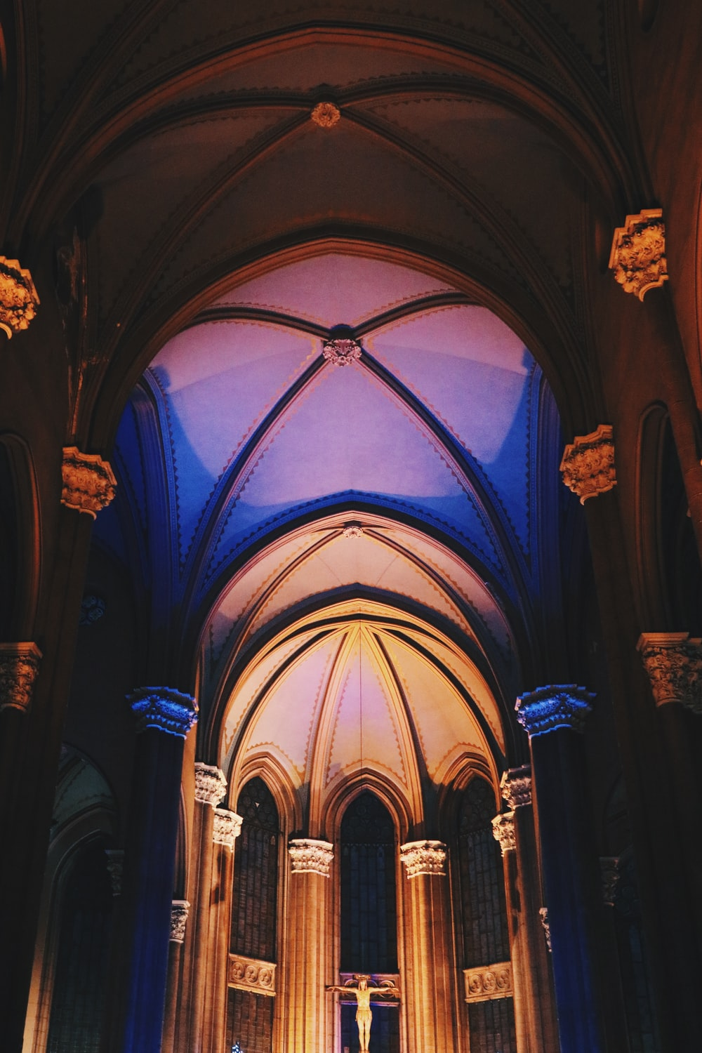 man in black robe standing inside blue and brown cathedral