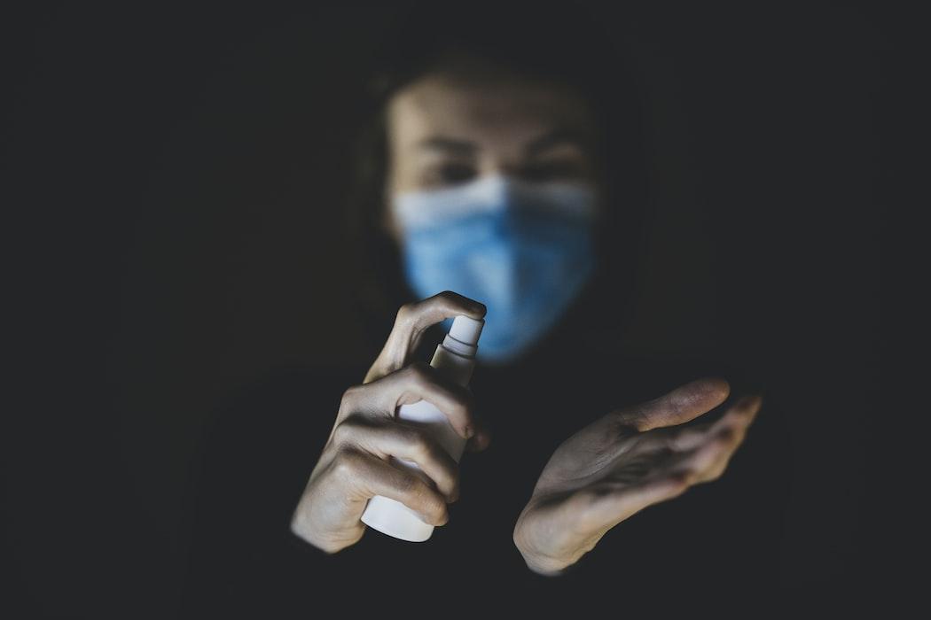 persona con cubrebocas aplicando desinfectante en las manos