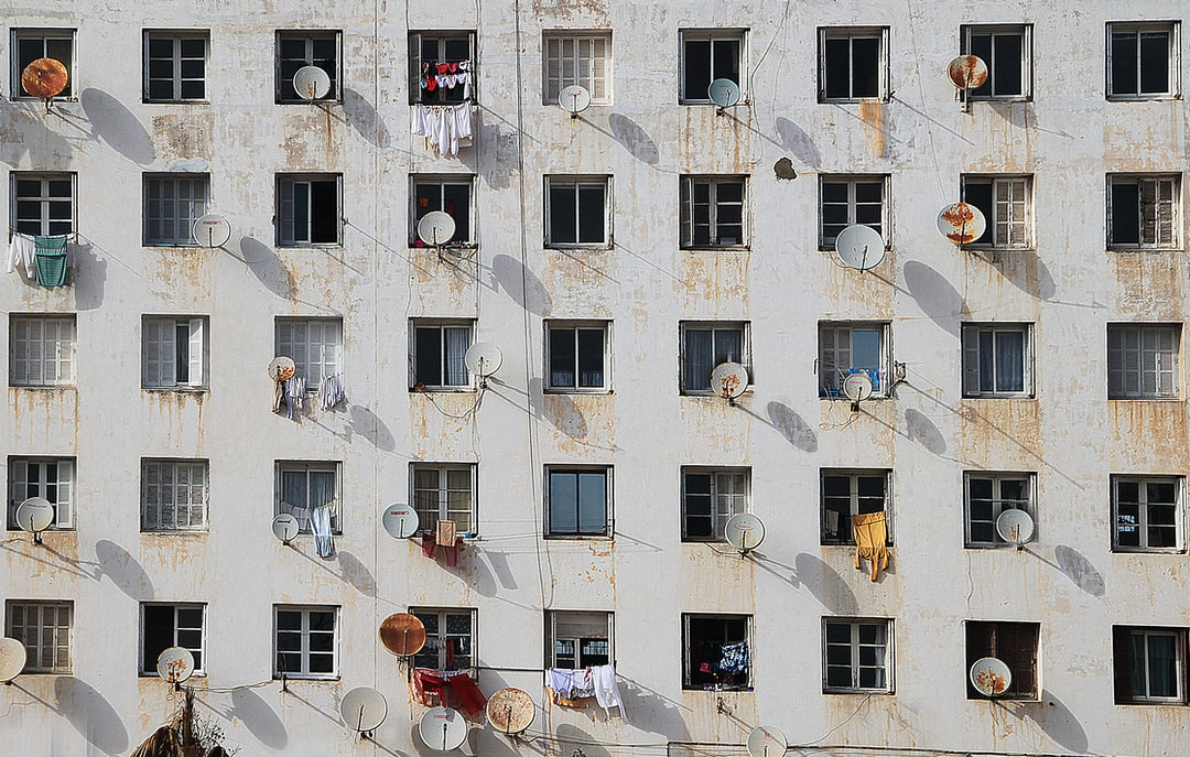 Geometric windows in a white building with satellite dish