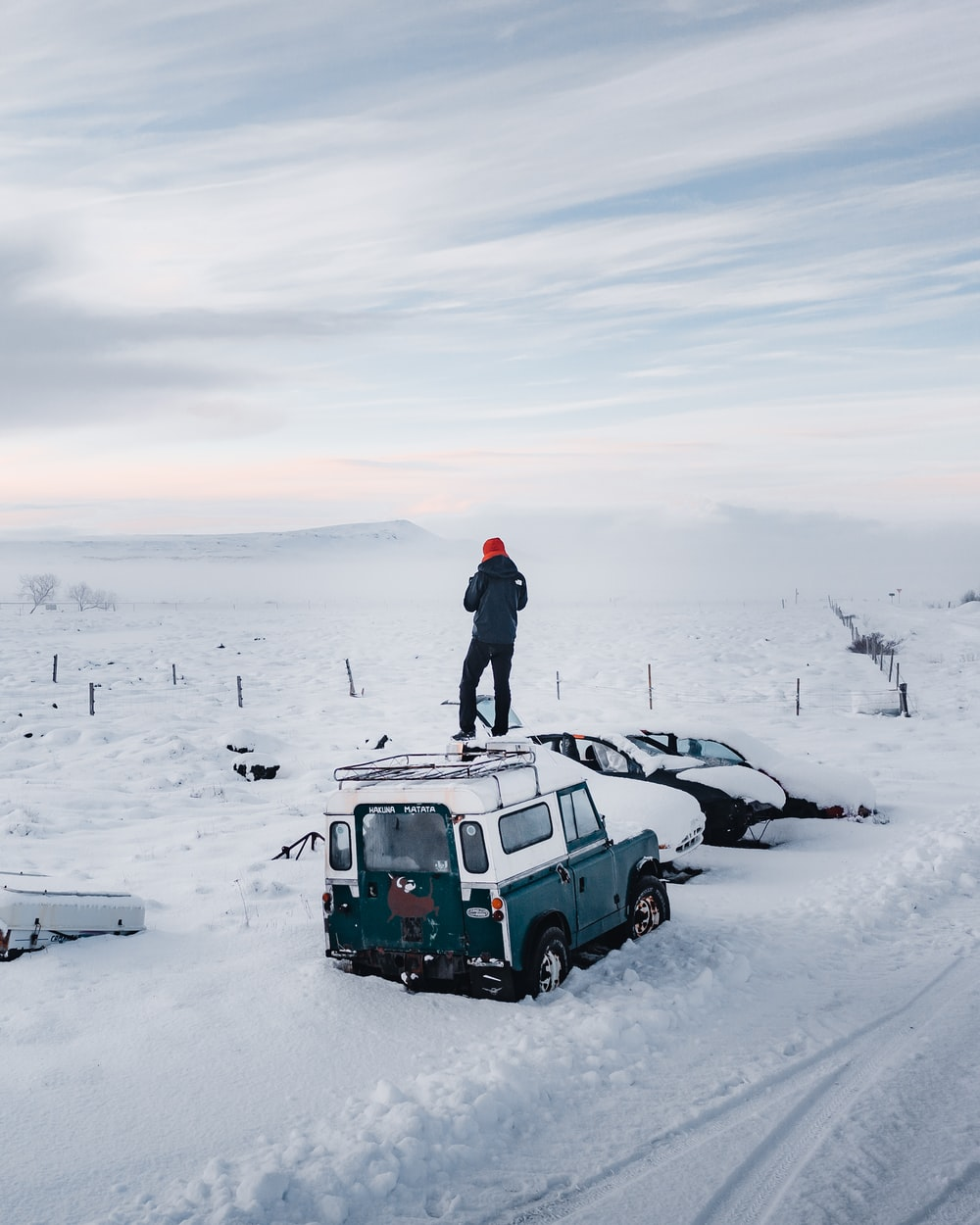 man in black jacket standing on green car on snow covered ground during daytime