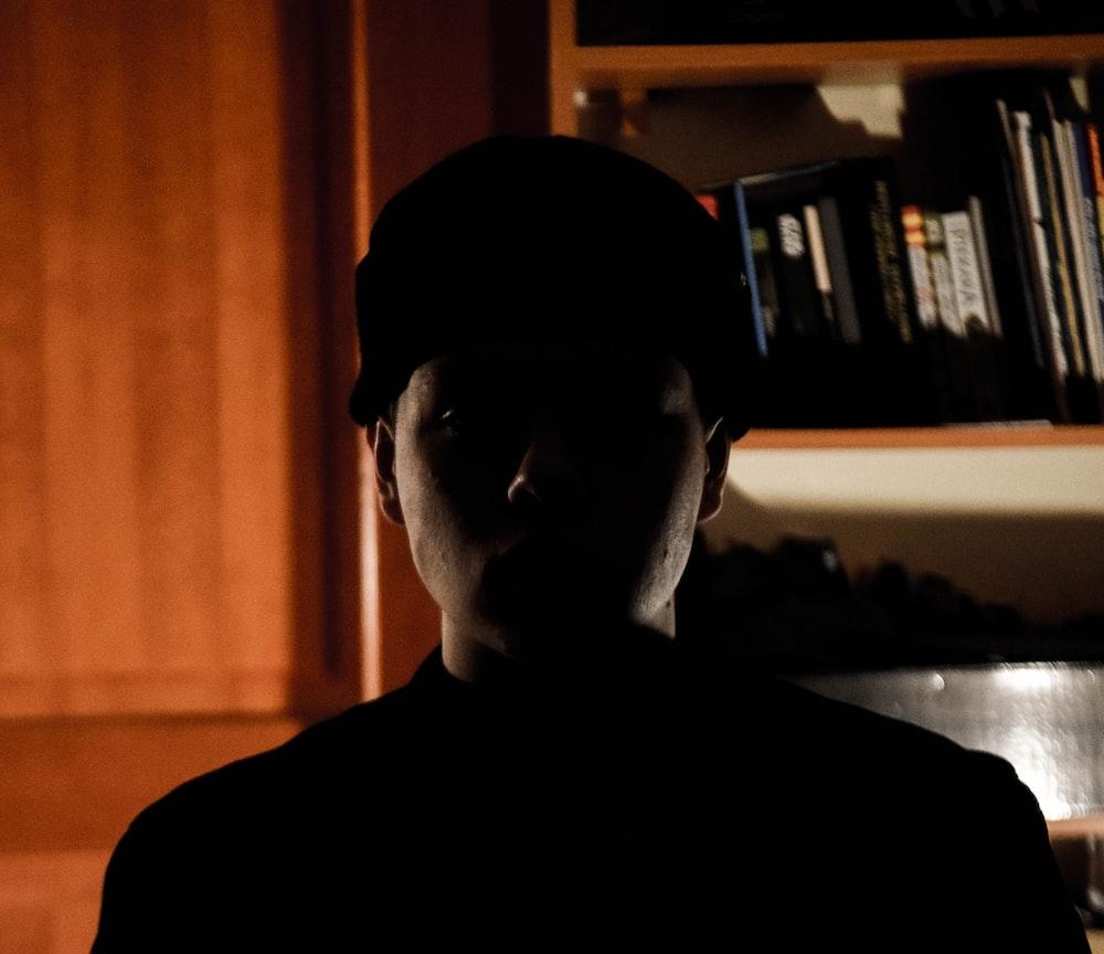 man in black crew neck shirt wearing black cap