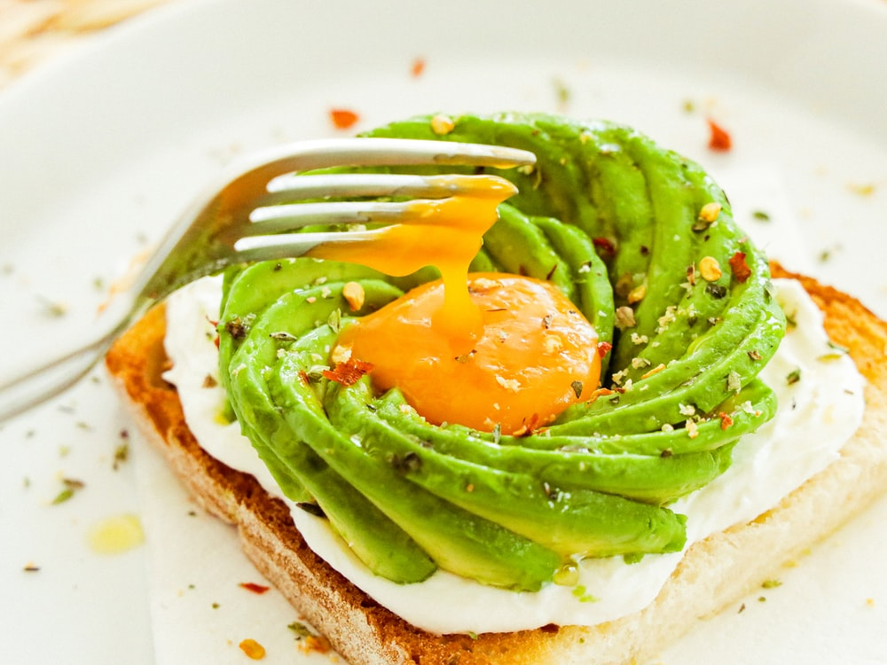 sliced tomato on bread with green vegetable on white ceramic plate