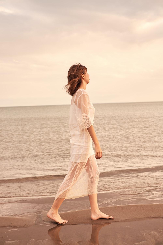 woman in white dress walking on beach during daytime