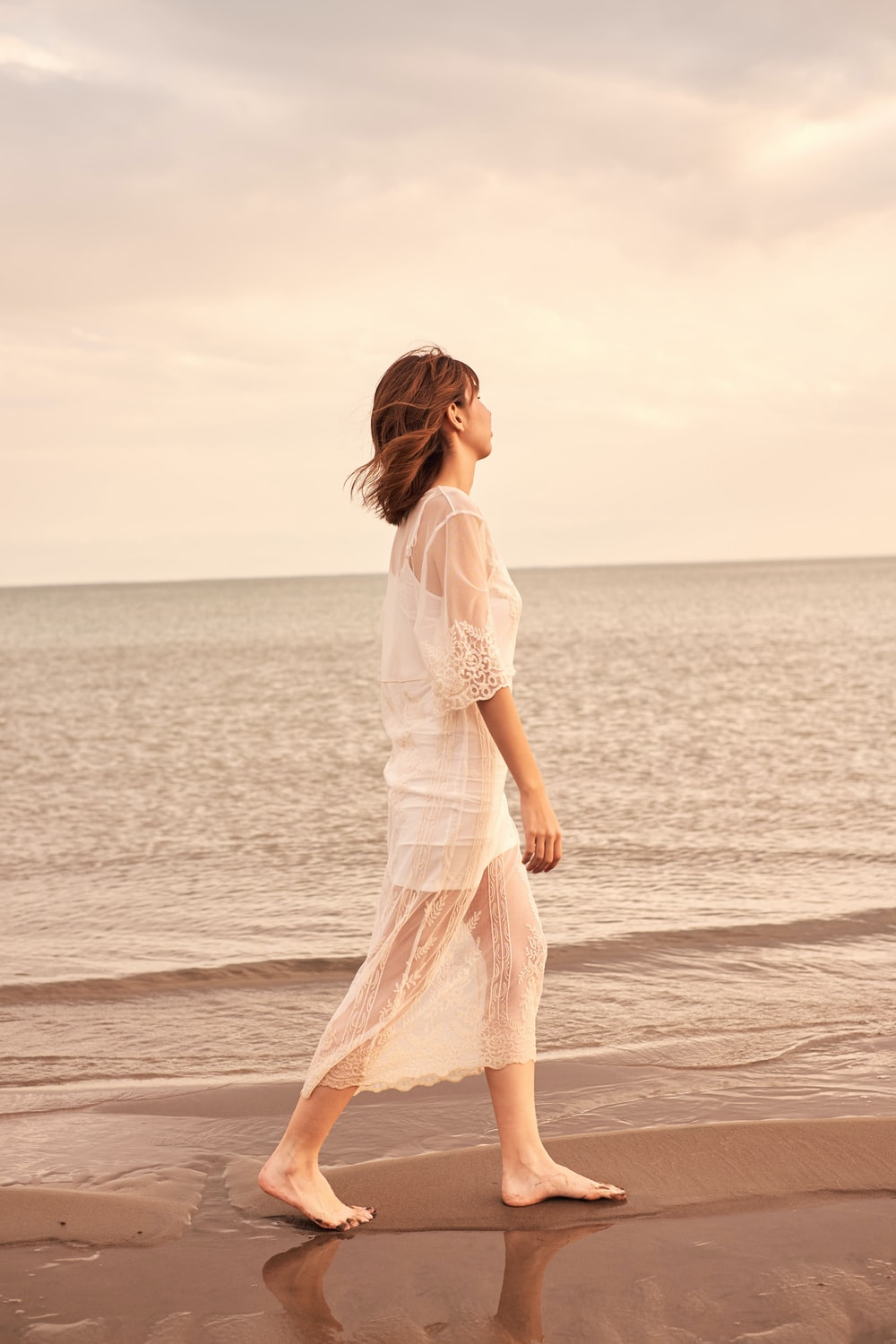 woman in white dress walking on beach during daytime