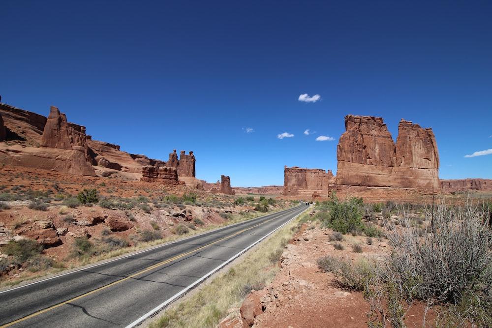 brown rock formation near gray asphalt road under blue sky during daytime