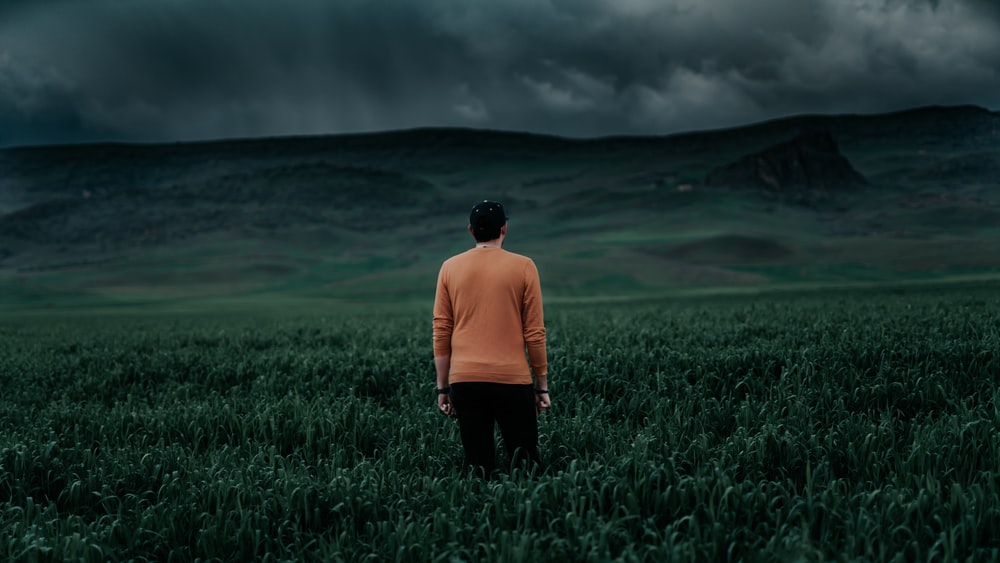 man in orange long sleeve shirt standing on green grass field