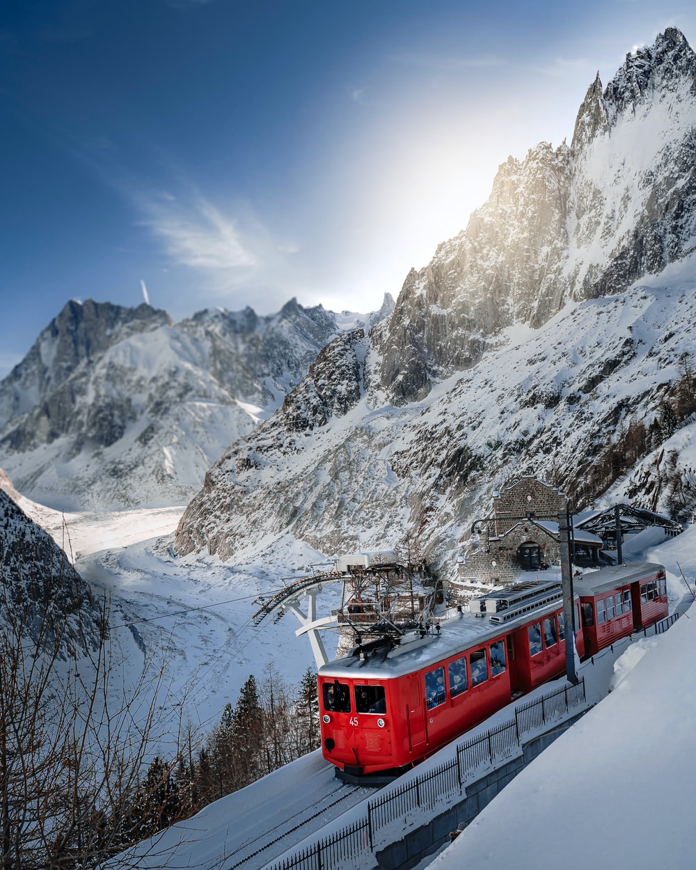 red and white train on snow covered mountain during daytime