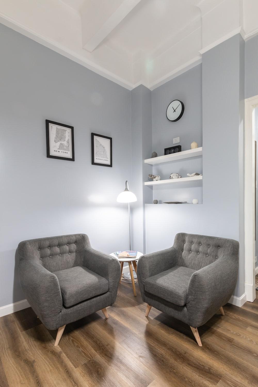 gray sofa chair beside white floor lamp