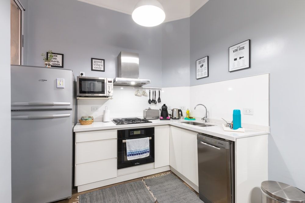 white top mount refrigerator beside white microwave oven