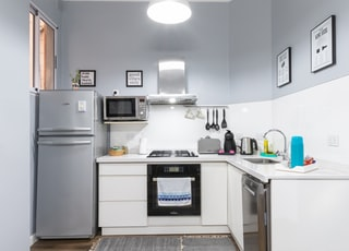 white top mount refrigerator beside white wall