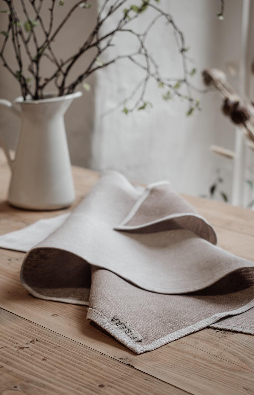 white ceramic vase on brown wooden table