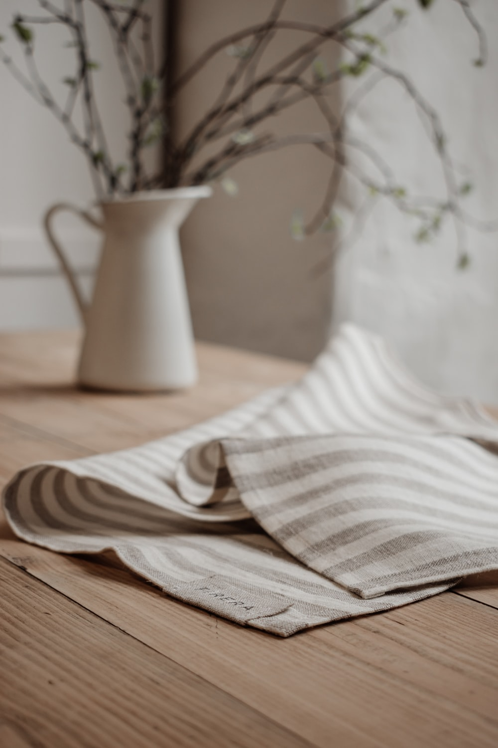 white and brown stripe textile on brown wooden table