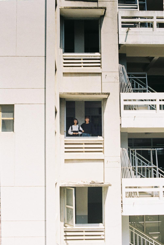 man in white shirt sitting on white concrete window during daytime