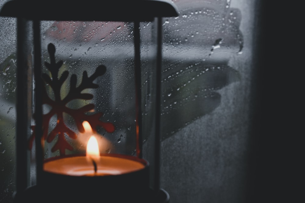 lighted candle on black candle holder