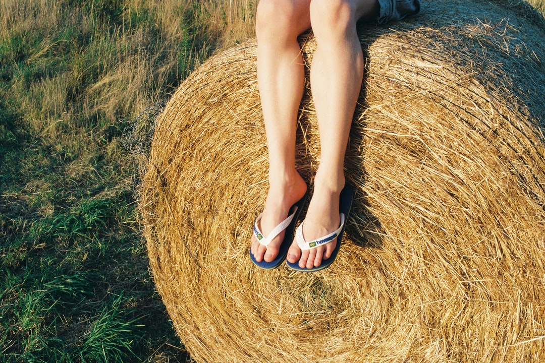 A child sitting on a hay bale. They are wearing flip flops on their feet. Shot on film.