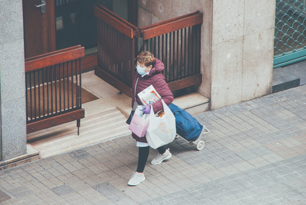 woman in pink long sleeve shirt carrying baby in white stroller