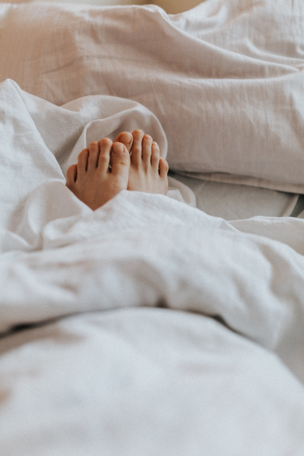 person lying on white bed