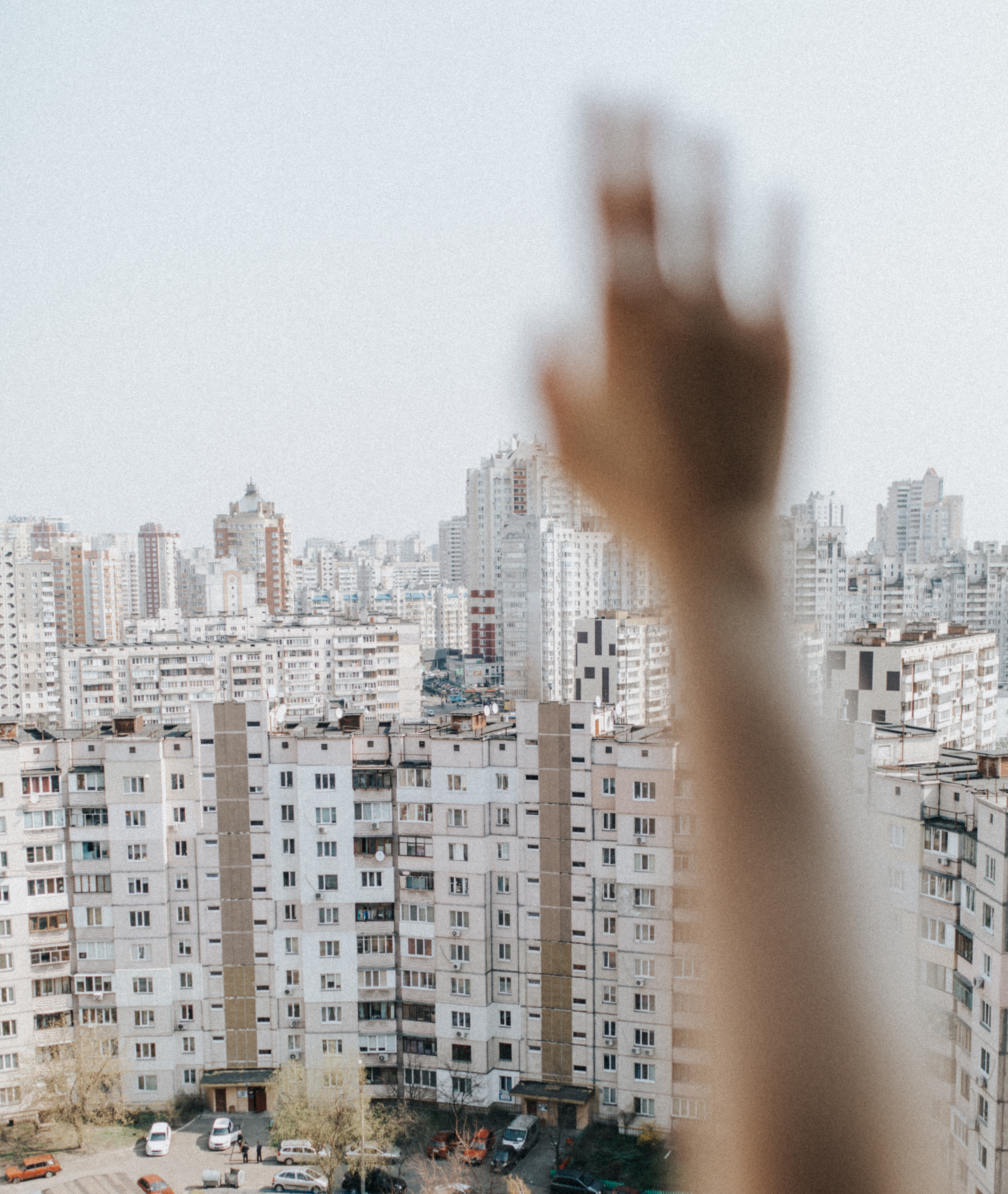 person raising hand in front of white concrete building during daytime