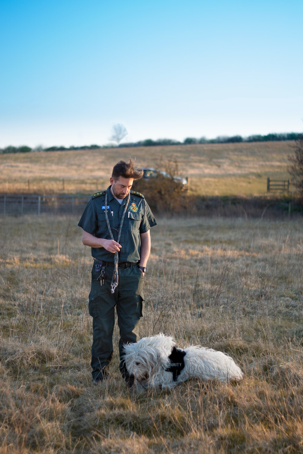 man in black polo shirt standing beside white long coated dog on brown grass field during