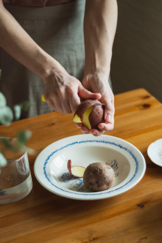 person holding sliced fruit on white ceramic plate
