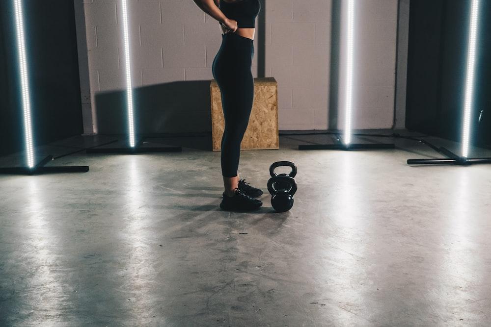 woman in black tank top and black leggings standing on white floor