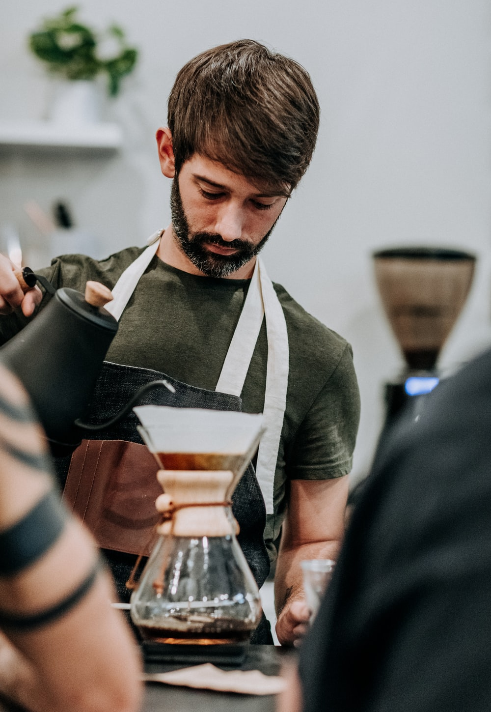 man in black apron holding black and white ceramic cup