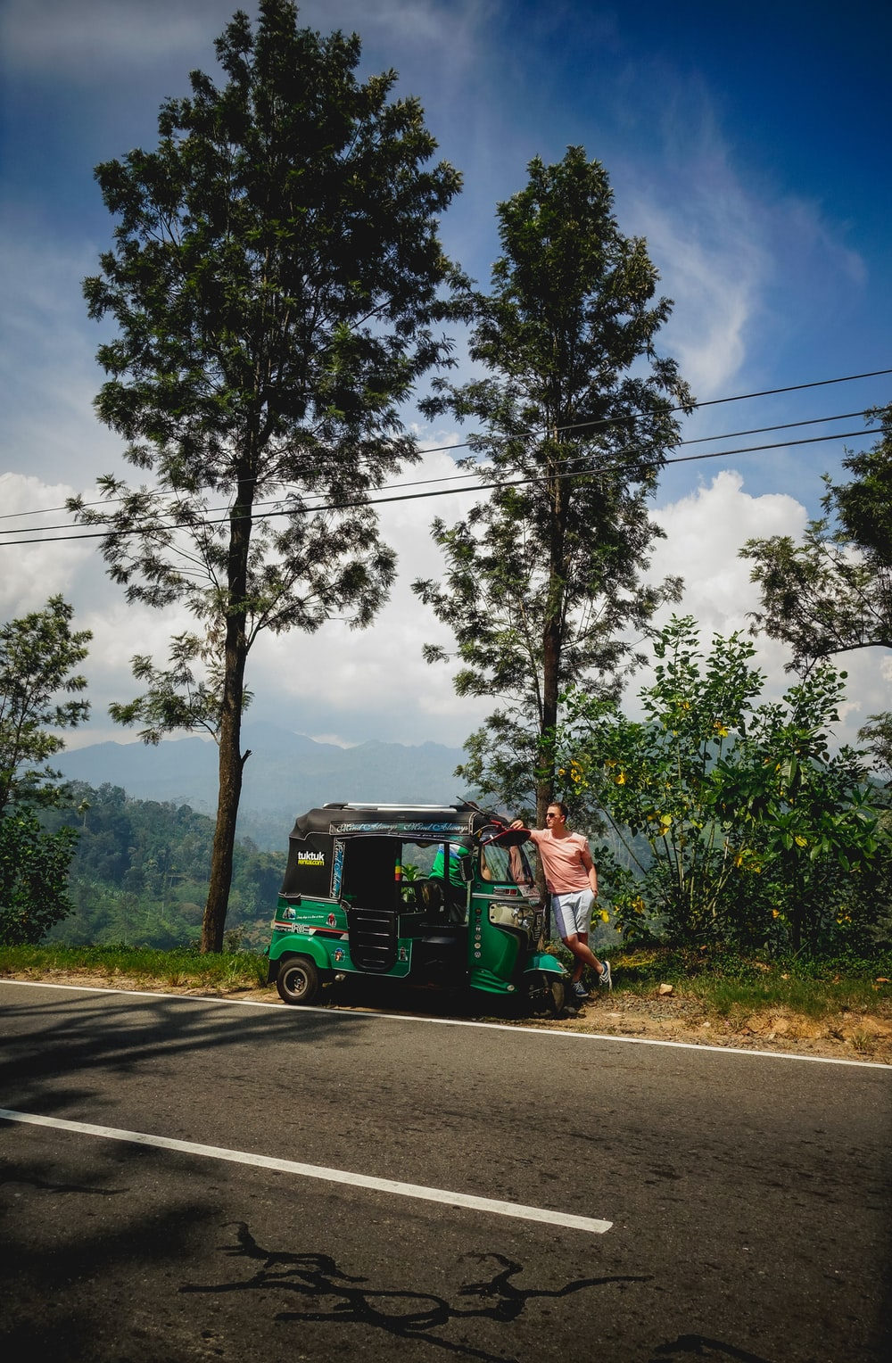 man in green jacket riding green and black auto rickshaw on road during daytime