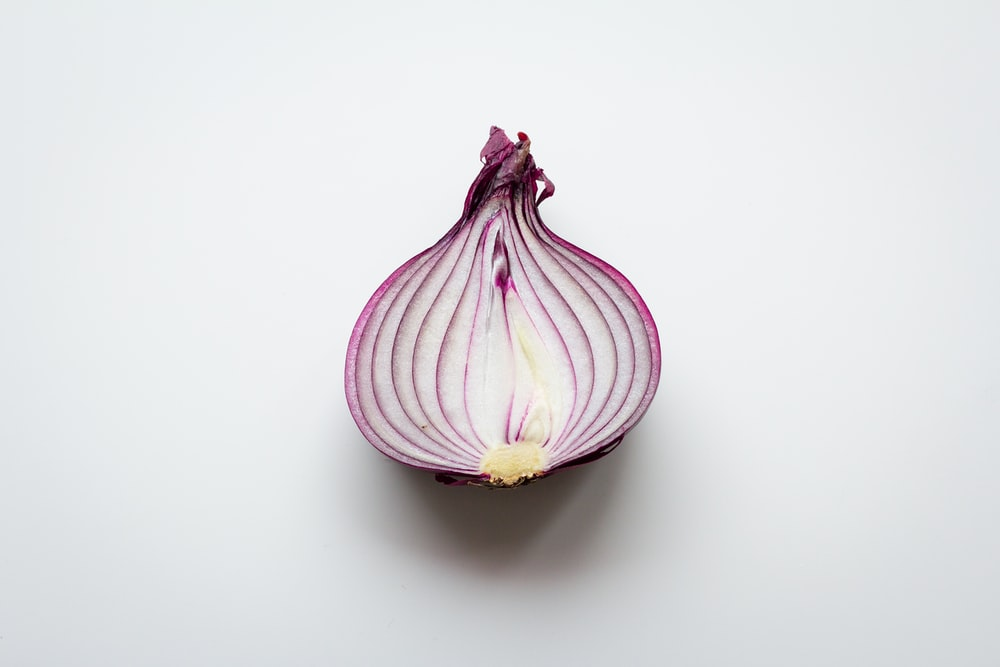 pink and white garlic on white surface