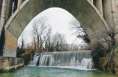 water falls under white arch bridge