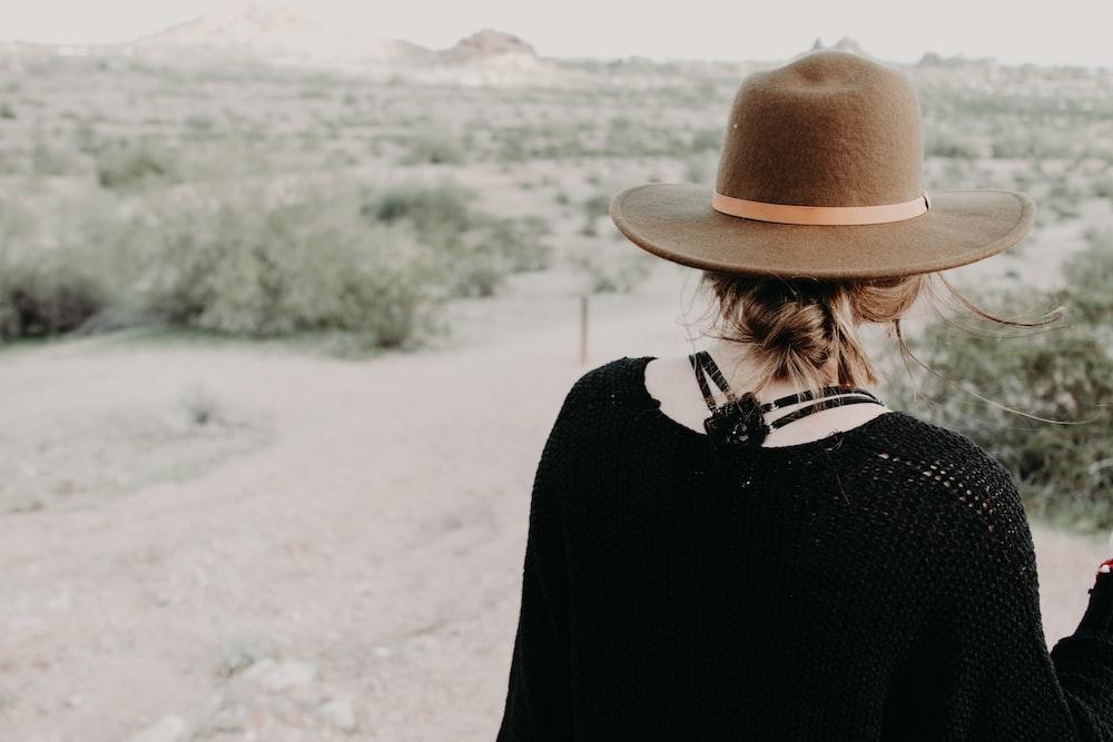 woman in black long sleeve shirt wearing brown hat