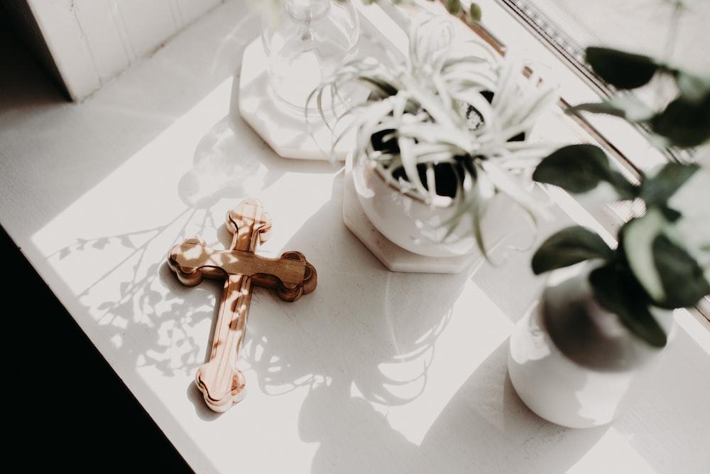 brown wooden cross on white ceramic mug