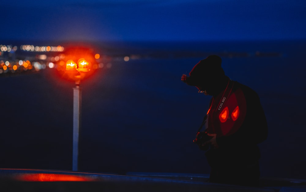 man in black jacket standing on the bridge during night time
