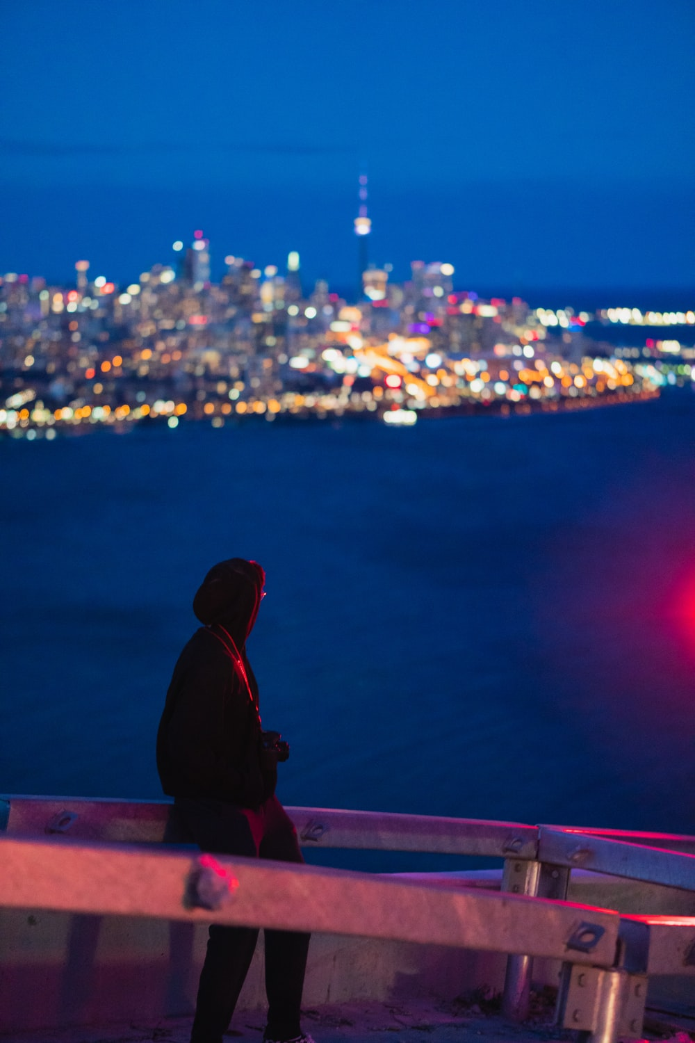 man in black hoodie sitting on brown wooden bench looking at city lights during night time