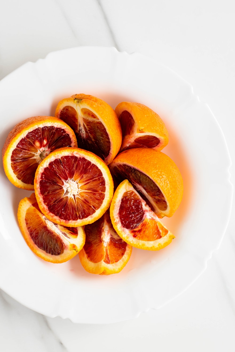 sliced orange fruit on white ceramic plate