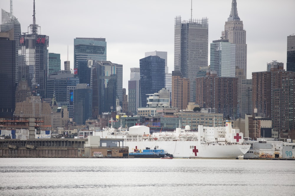 white ship on body of water near city buildings during daytime