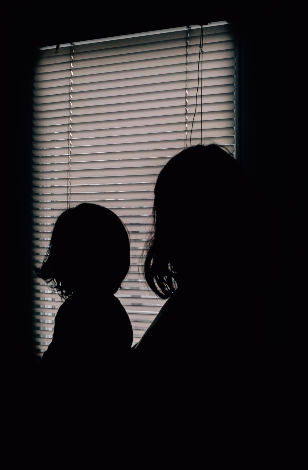 silhouette of 2 women standing near window with white window blinds