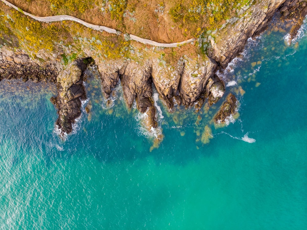 aerial view of green and brown rocky mountain beside blue body of water during daytime