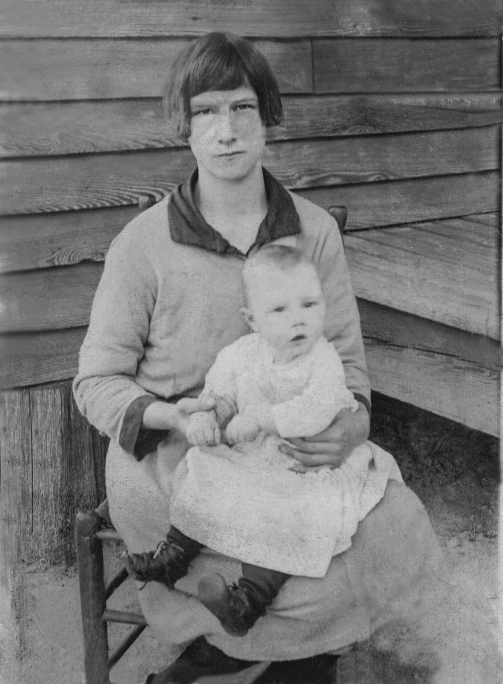 woman in sweater carrying baby in grayscale photography