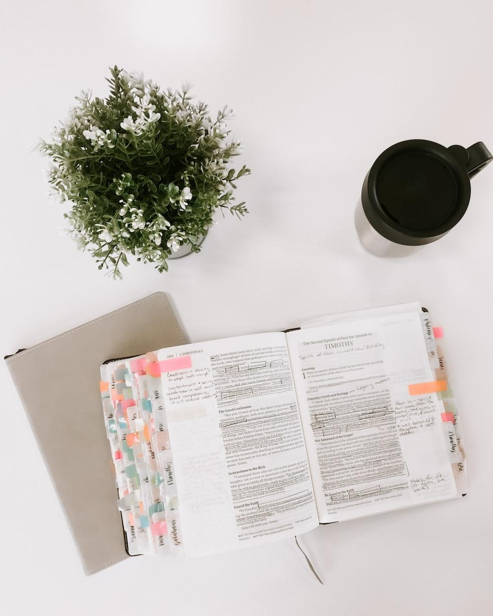 white printer paper beside black ceramic mug on white table