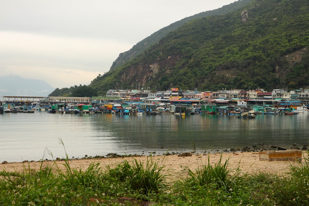 boats on sea near green mountain under white sky during daytime