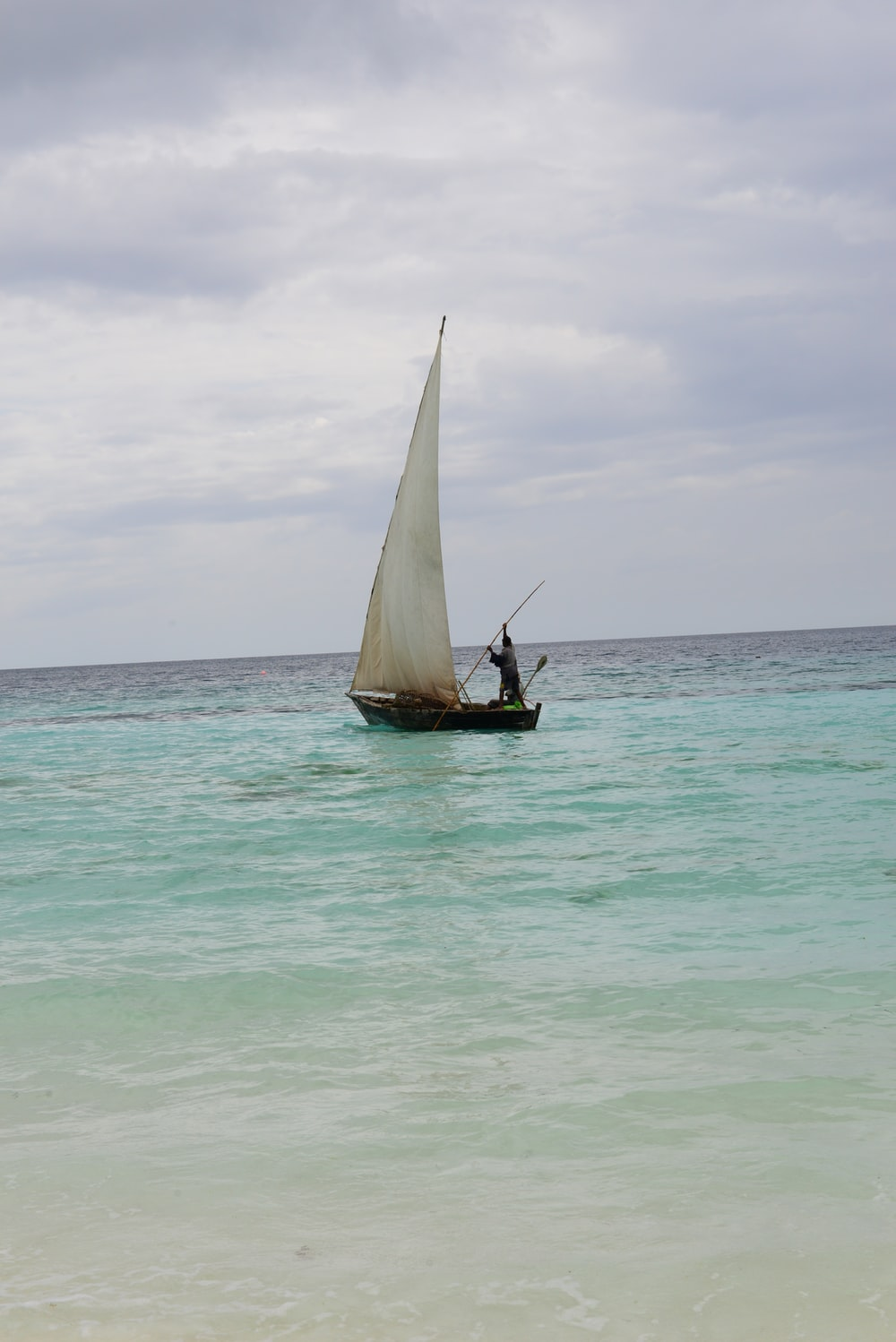 brown and white sail boat on sea during daytime