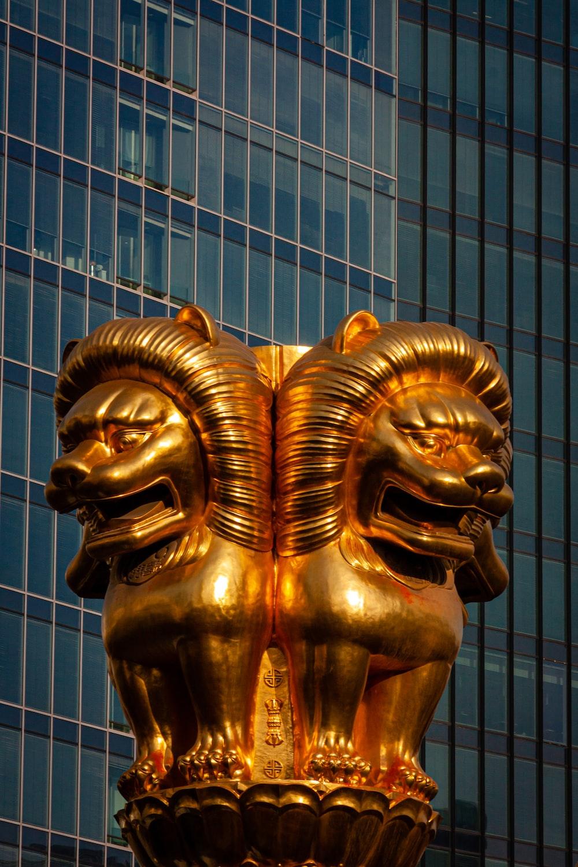 gold lion statue near blue building