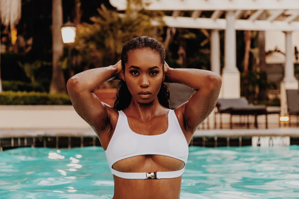woman in white bikini top standing on swimming pool during daytime