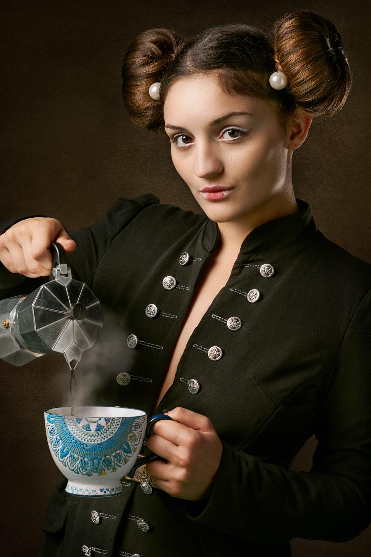 woman in black coat holding blue and white ceramic mug