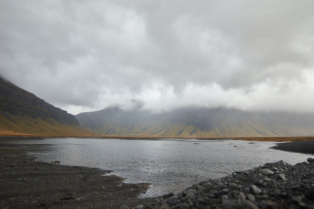 brown mountain near body of water under white clouds during daytime