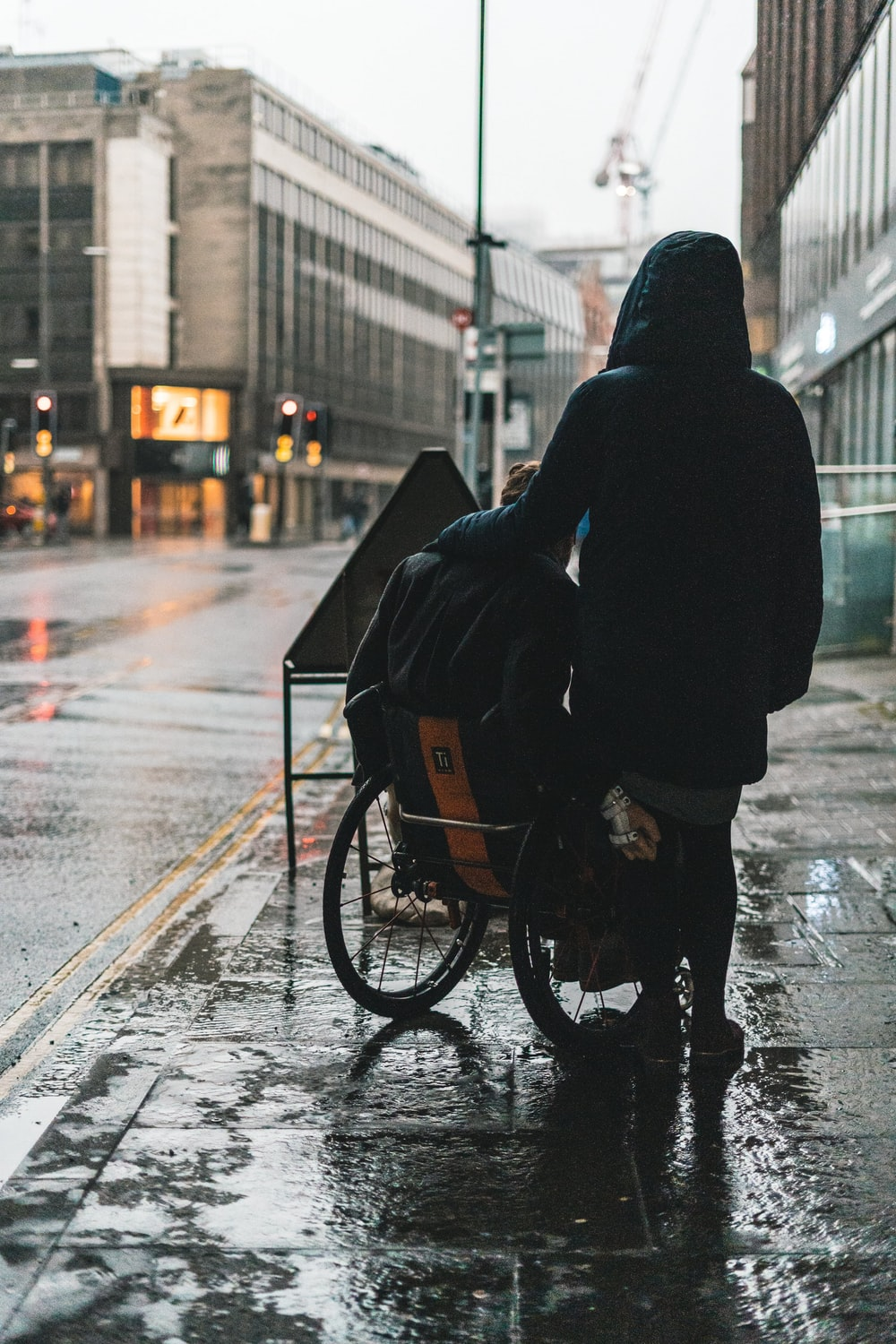 person in black hoodie riding bicycle on road during daytime