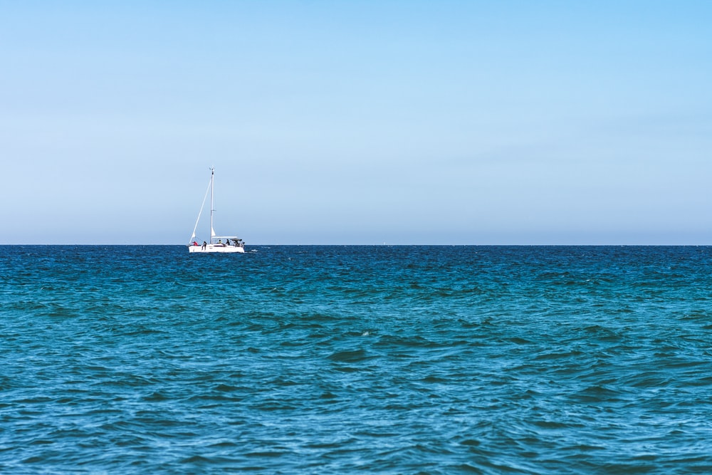 white boat on sea under gray sky