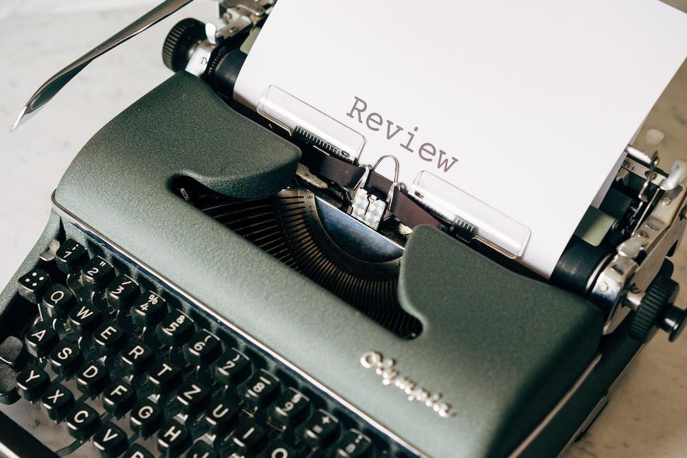 白いテーブルの上の黒と白のタイプライター